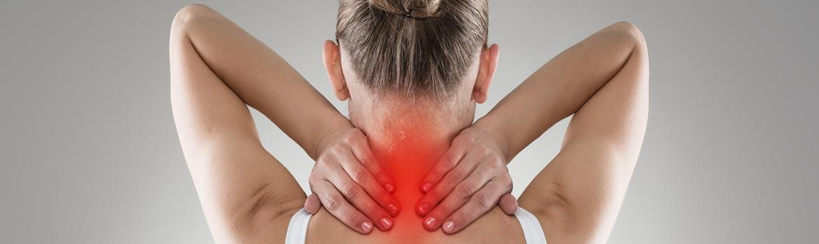 woman holding the back of her neck in pain