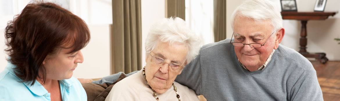 Older couple in their home talking to a community nurse